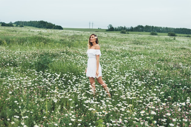 Een vrouw in een veld met kamilles