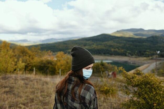 Een vrouw in een warme muts met een medisch masker op haar gezicht in het bos in de natuur.