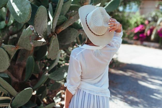 Een vrouw in een wit overhemd en een hoed staat naast een cactus