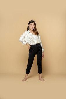 Een vrouw in een wit overhemd en een zwarte broek staat met haar handen in de taille