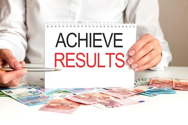 Een vrouw in een wit overhemd houdt een vel papier vast met de tekst: achieve results