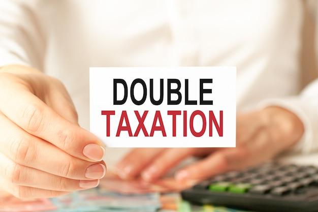 Een vrouw in een wit overhemd houdt een vel papier vast met de tekst: dubbele belasting, bedrijfsconcept.
