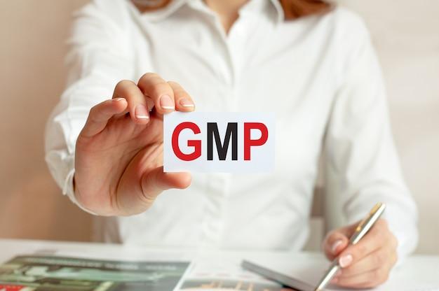 Een vrouw in een wit overhemd houdt een vel papier vast met de tekst: gmp.