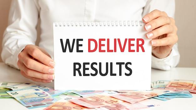 Een vrouw in een wit overhemd houdt een vel papier vast met de tekst: we deliver results. bedrijfsconcept voor bedrijven en onderwijsinstellingen. bankbiljetten en tablet op een tafel, achtergrond.
