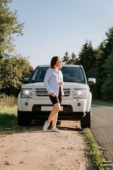 Een vrouw in een wit overhemd naast een witte auto op de weg