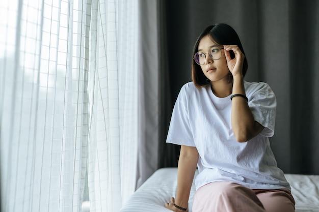 Een vrouw in een wit overhemd op het bed zitten en uitkijken.