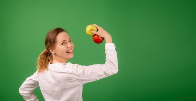 Een vrouw in een wit overhemd toont de kracht van appels op een groene achtergrond. het concept van voeding, gezonde voeding, vegetarisme.