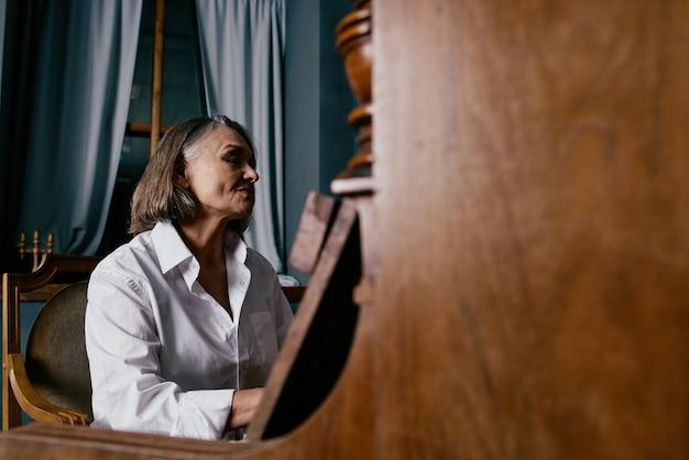 Een vrouw in een wit overhemd zit op een stoel naast een piano en leert muziek