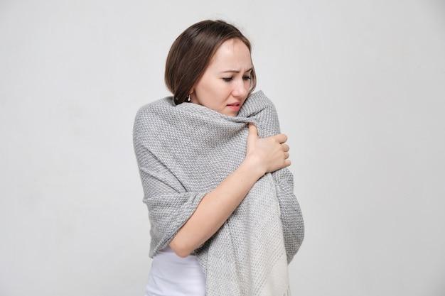Een vrouw in een wit shirt droeg een sjaal van de kou en koude rillingen. verkoudheid en griep concept.