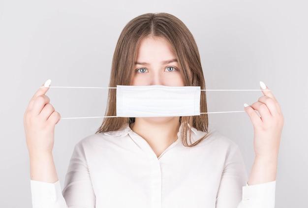 Een vrouw in een witte blouse draagt een antivirusmasker om te voorkomen dat anderen anderen besmetten met het coronavirus covid-19 en sars cov 2