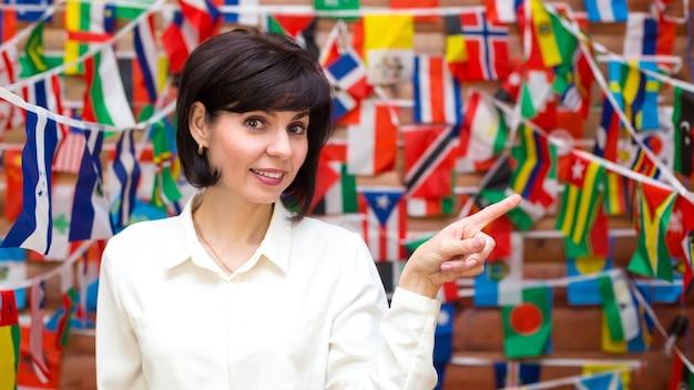 Een vrouw in een witte blouse wijst met haar vinger tegen de achtergrond van de vlaggen van de hele wereld