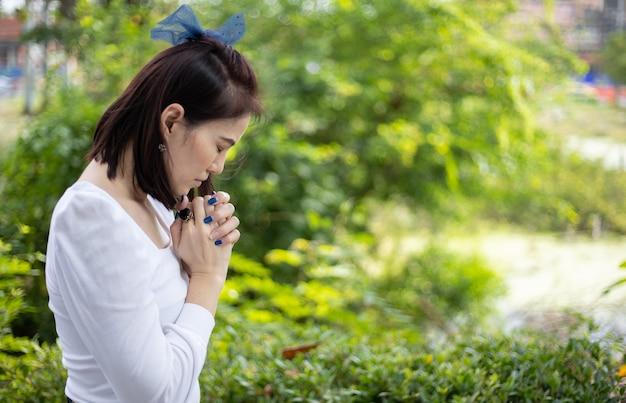 Een vrouw in een witte jurk die in de tuin onder het zonlicht bidt.