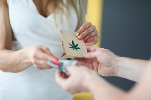Een vrouw in een witte jurk geeft geld en ontvangt een zak marihuana die de bestelling bezorgt