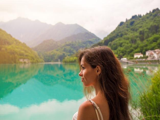Een vrouw in een zomerjurk staat op de brug bij azuurblauw bergmeer in italië, dolomieten