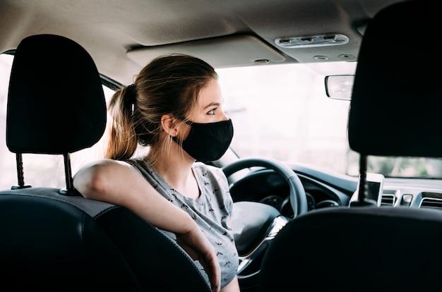 Een vrouw in een zwart medisch masker met blond haar zit in een auto met het stuur links