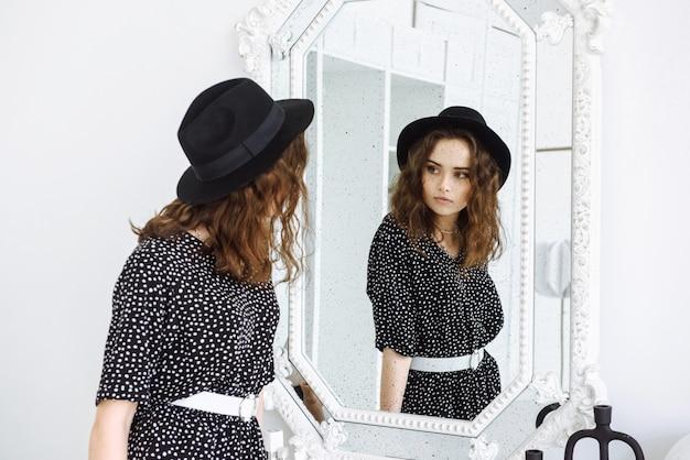 Een vrouw in een zwarte jurk en hoed kijkt in de spiegel en ziet haar spiegelbeeld met veel zwarte stippen als sproeten op haar gezicht