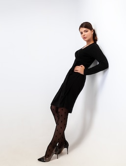Een vrouw in een zwarte jurk leunde met haar rug tegen een muur op een witte muur