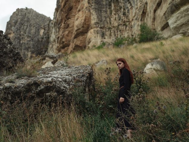 Een vrouw in een zwarte jurk loopt in de herfst in de bergen over de natuur