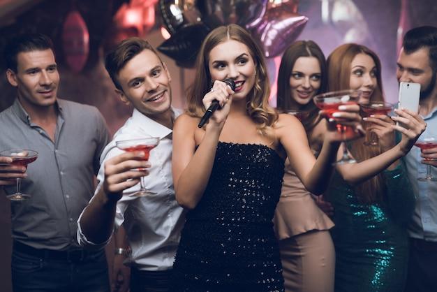 Een vrouw in een zwarte jurk zingt liedjes met haar vrienden.