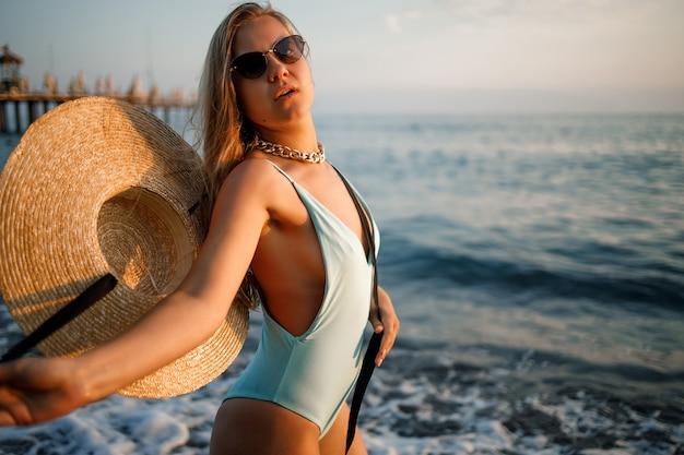 Een vrouw in een zwempak en een hoed met bril loopt langs het strand bij zonsondergang. het concept van zeerecreatie. selectieve focus
