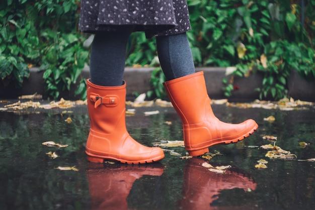 Een vrouw in felroze rubberlaarzen (rubberlaarzen) onder de regen. herfst concept