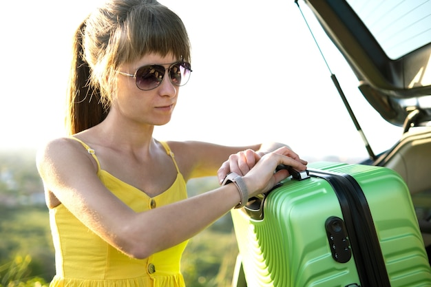 Een vrouw in gele jurk die groene koffer uit de kofferbak haalt.