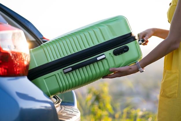 Een vrouw in gele jurk die groene koffer uit de kofferbak neemt. reizen en vakanties concept.