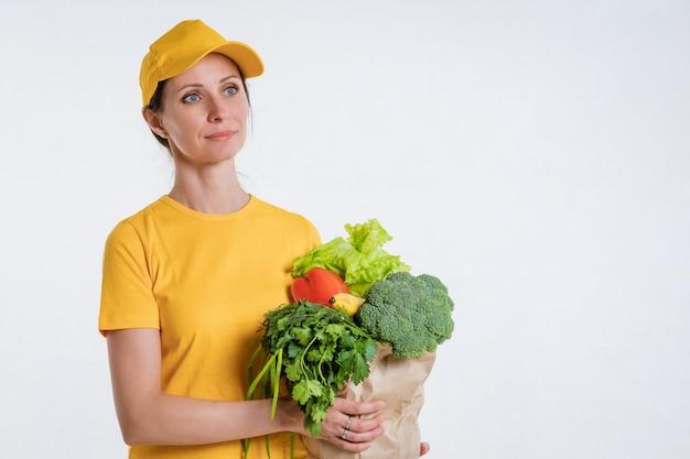 Een vrouw in gele kleren, die een pakket voedsel, op een witte achtergrond levert