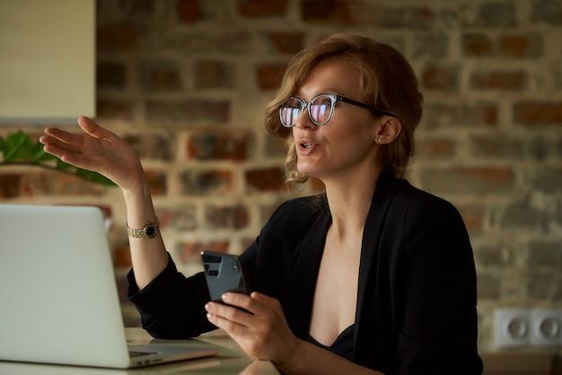 Een vrouw in glazen werken op afstand met een smartphone op een laptop in de avond. een dame die een probleem met collega's bespreekt tijdens een videoconferentie thuis.