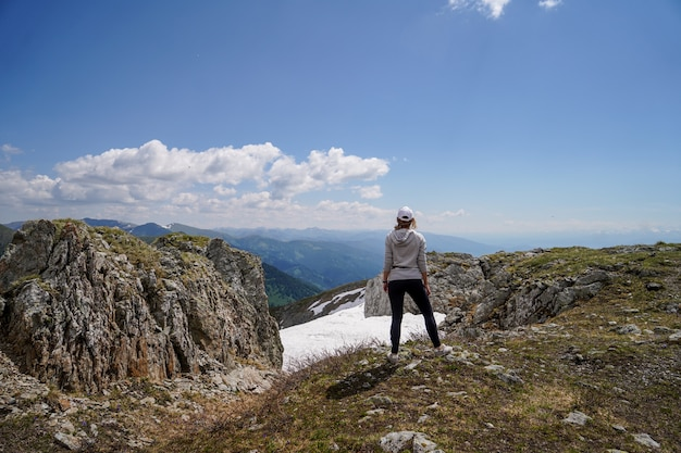Een vrouw in grijze hoody die zich op rotsen voor hemelachtergrond bevindt