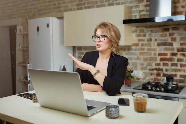 Een vrouw in haar keuken werkt op afstand op een laptop. een blond meisje in glazen gebaren tijdens een gesprek met haar collega's in een videogesprek thuis.
