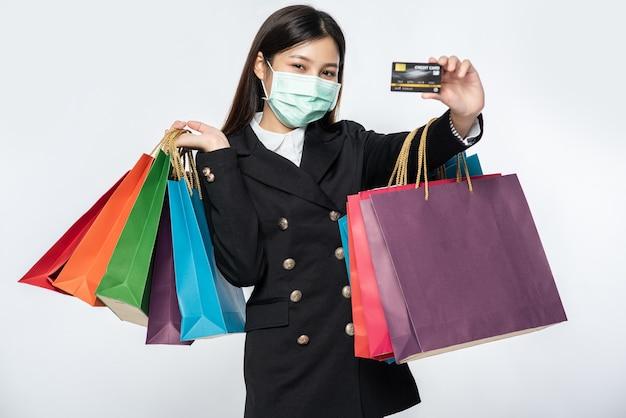 Een vrouw in het donker met een masker loopt winkelen, heeft creditcards en heel veel tassen