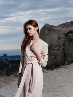 Een vrouw in lichte kleren in de bergen in de natuur en hoge rotsen. hoge kwaliteit foto