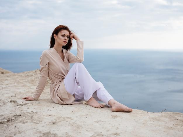 Een vrouw in lichte kleren zit op een rots met de oceaan in de