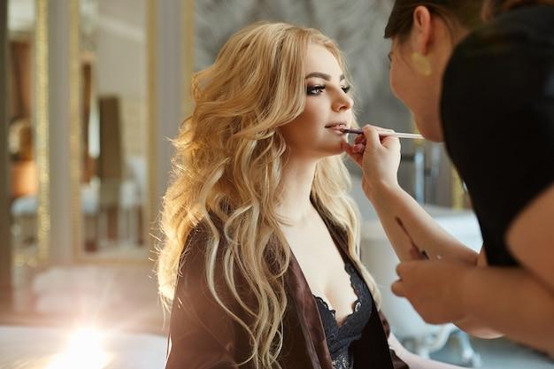 Een vrouw in lingerie die make-up doet om zich voor te bereiden op de bruiloft