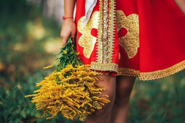 Een vrouw in nationale russische kleren met een mooi boeket gele bloemen in haar hand