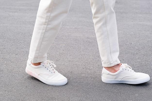 Een vrouw in sportschoenen staat op de stoep. benen van een meisje in nieuwe witte sneakers en jeans. modieuze en stijlvolle levensstijl.