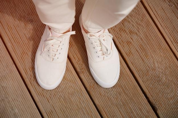 Een vrouw in sportschoenen staat op de stoep of houten stoep. benen van een meisje in nieuwe witte sneakers en jeans. modieuze en stijlvolle levensstijl.