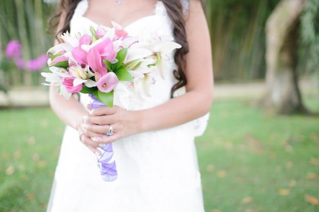 Een vrouw in trouwjurk met een boeket bloemen in haar handen