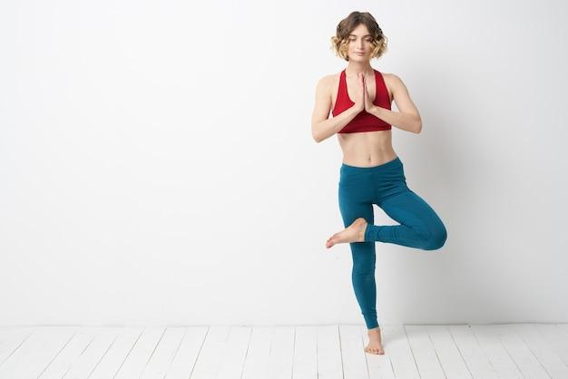 Een vrouw in volle groei in een lichte kamer houdt yogameditatie zich bezig met sport.