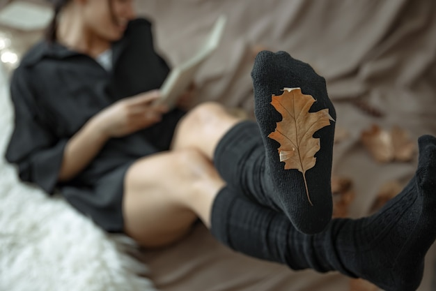 Een vrouw in warme kousen op een onscherpe achtergrond en een herfstblad in focus.