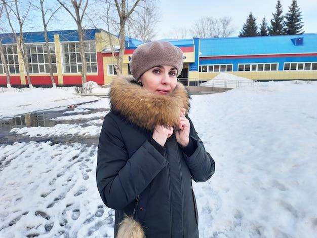 Een vrouw in winterkleren staat in de sneeuw bij een stadsschool
