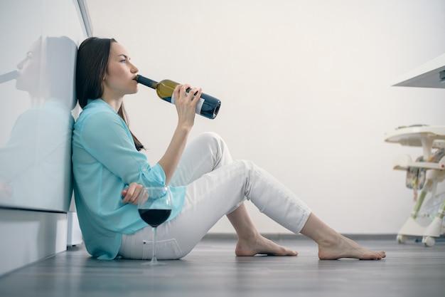 Een vrouw in witte spijkerbroek en een turquoise shirt zit op de vloer in het interieur van een witte keuken en drinkt rode wijn uit een fles, scheiding, alcohol, afscheid, verdriet, afhankelijkheid, vermoeidheid