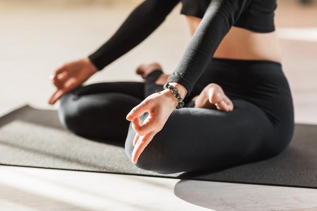 Een vrouw in zwarte sportkleding die yoga beoefent, houdt zich bezig met meditatie in de lotuspositie en voert het kin mudra-symbool uit met haar handen