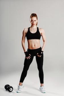 Een vrouw in zwarte sportkleding vormt, pronken met haar spieren en buikspieren op een witte achtergrond.