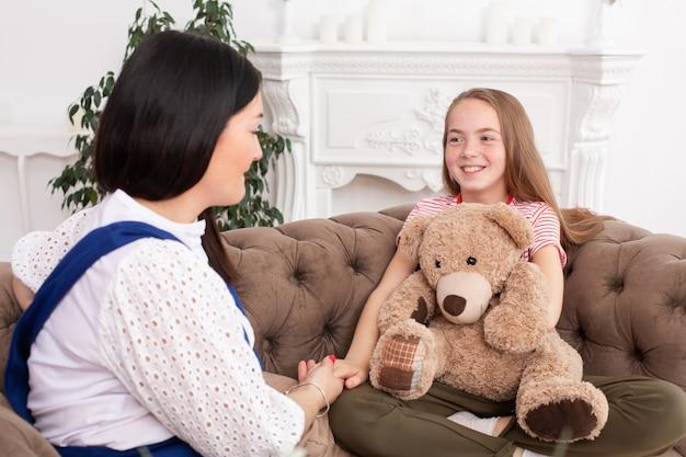 Een vrouw is een professionele kinderpsycholoog in gesprek met een tienermeisje in haar gezellige kantoor