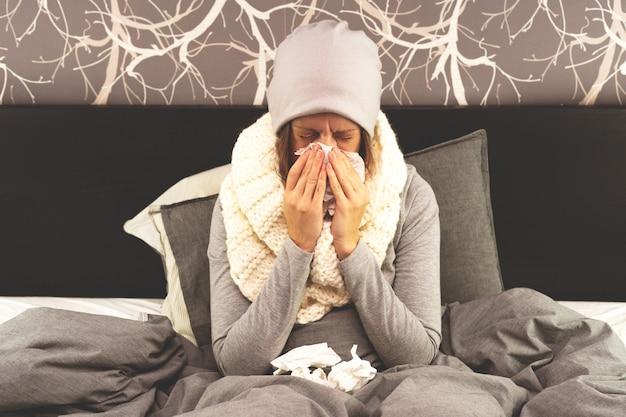 Een vrouw is thuis ziek, loopneus en griep. warm gekleed en bedekt met een deken.