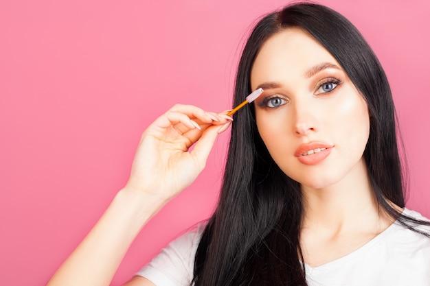 Een vrouw kamt haar wimpers met een mascaraborstel, gezichtsclose-up, op een roze muur, met exemplaarruimte. het concept van uitbreiding of mascara en make-up.