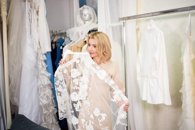 Een vrouw kiest kleding in een atelier of winkel.