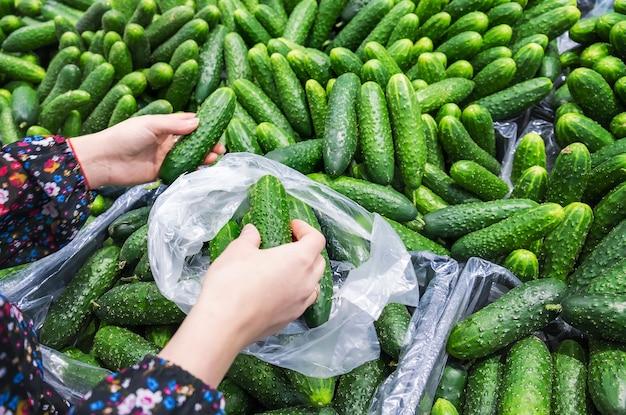 Een vrouw kiest komkommers in een supermarkt. selectieve aandacht. eten.